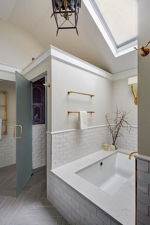 Vaulted Ceiling In A Master Bathroom Features A Skylight Over A