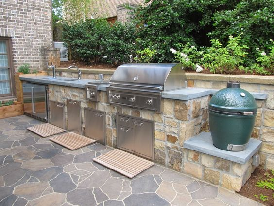 A custom made outdoor kitchen an ashlar fieldstone veneer, granite countertop, a Lynx grill and appliances, and a Big Green Egg smoker. The patio is made from Belgard Mega Arbel concrete pavers and there are custom made cedar planter boxes for culinary herbs at one end of the kitchen unit.