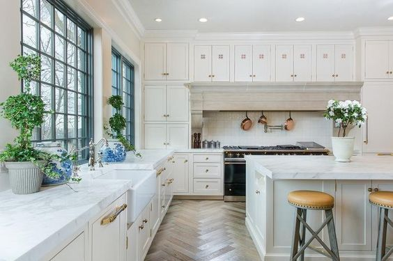 Lined with herringbone wood floors, this beautiful transitional kitchen features a gorgeous farmhouse sink fitted with a polished nickel hook and spout faucet positioned in front of a blue framed window flanked by white honed marble countertops sat on white shaker cabinets finished with nickel and brass pulls.