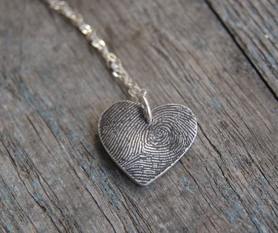 To create this small necklace, a fingerprint impression is molded in fine silver and hand-cut into a free-form symmetrical heart; as a result, the heart shape may vary a bit. I cut each of these pendants to optimize the amount of print that I can include. After firing, the entire pendant is oxidized (or darkened), hand polished, and tumbled to create a beautiful patina that highlights all of the unique ridges and valleys of your loved one's fingerprint. A sterling silver jump ring is ...