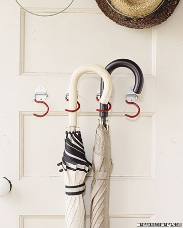 Using broom hooks behind a door to hang umbrellas. What a great idea! Then you'll never forget them if it's raining.
