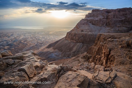 Looking out at sunrise over the Judean desert we can see the Dead Sea in the distance and the mountain of Masada, Herod's fortress and where the Jewish freedom fighters made their last stand in 72 A.D..