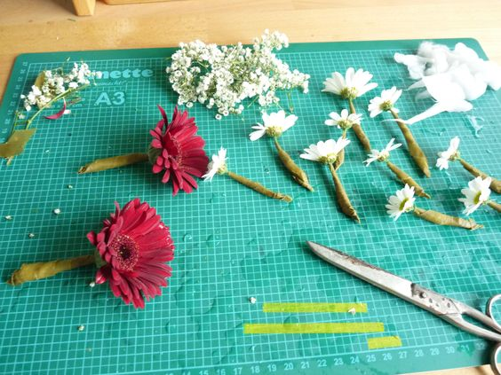 Blumenkranz sleber machen: Offener Ring aus Draht. Mit Floristenkrepp Blumenstiele umwickeln. Dann mit Draht um den Drahtring binden. Mit Satinband Ring schließen.
