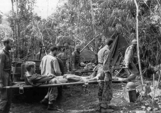 Unloading casualties at a Collecting Station. Litter bearers with patients in the jungle. Papua New Guinea, Solomon Islands, February 1944