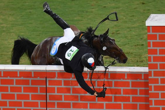 Czech Republic's Jan Kuf falls from his horse in the show jumping portion of the men's modern pentathlon event at the Deodoro Stadium during the Rio 2016 Olympic Games in Rio de Janeiro on August 20, 2016. / AFP / MANAN VATSYAYANA