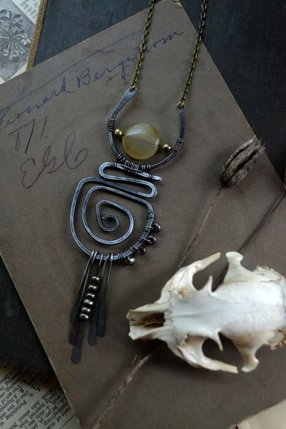 A new style necklace created with hammered steel that has been sanded down to give a worn rustic aesthetic,salvaged glass bead, vintage metal beads salvaged from old jewelry and little silver space...