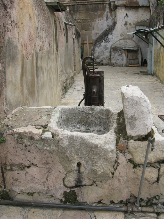 Old rusty pump and stone sink in Jerusalem