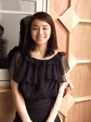 フリルの黒いドレスを着た石田ゆり子