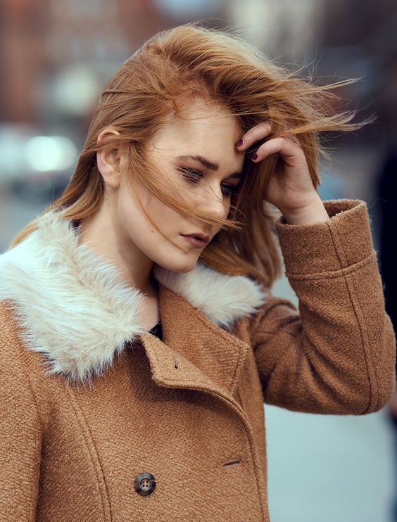 Portrait of redhead Christina Key. She is wearing a perfect winter outfit in Berlin