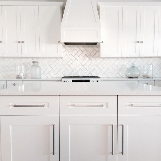 All White Kitchen Features White Shaker Cabinets Paired With White Quartz  Countertops And A White Subway ...