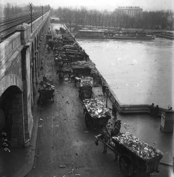Le déchargement des ordures dans la Seine, depuis le Viaduc d'Auteuil, en janvier 1910. Ne pouvant les évacuer normalement du fait des inondations, les éboueurs déverseront dans le fleuve, des tonnes d'ordures depuis des charrettes tirées par des chevaux.