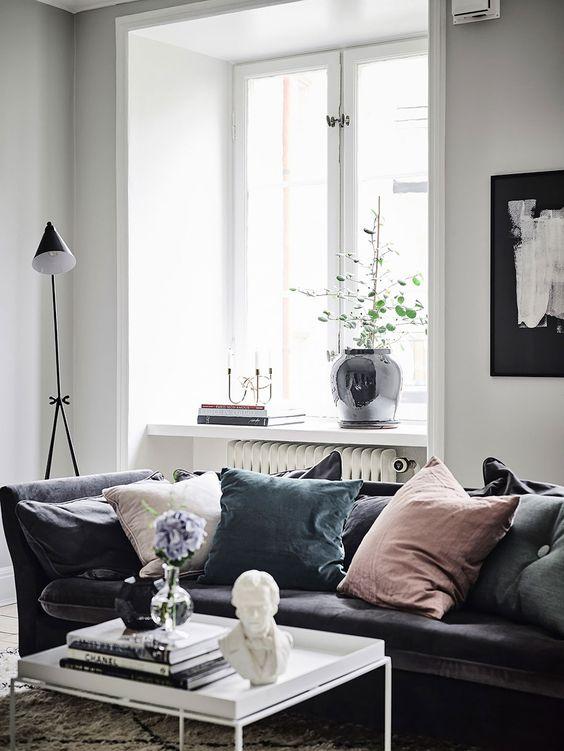 Dusky pink & blue velvet cushions on a dark grey velvet sofa