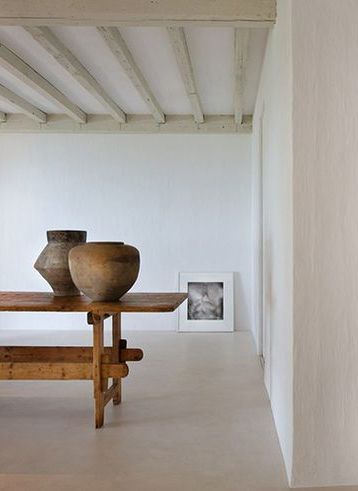 Minimal, simple interior design by #AXELVERVOORDT for Calvin Klein's home in Miami with #rusticdecor dinning table, beamed ceiling, concrete floor, and ancient pottery
