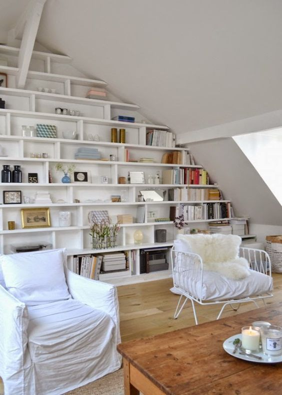 White living room with modern farmhouse style and a wall of built-in shelves in a Paris apartment (in the Marais) by Lucille Gauthier-Braud. #builtin #shelves #Parisapartment #livingroom