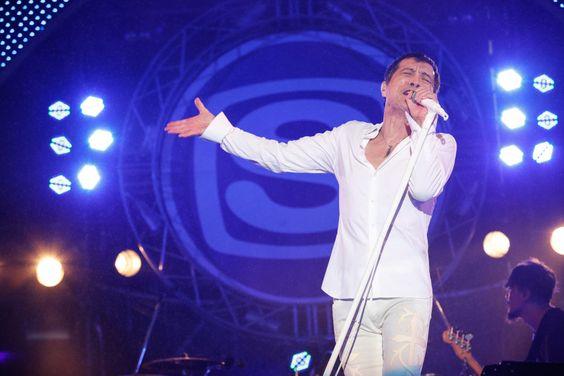 上下白い衣装を着て歌っている矢沢永吉の画像