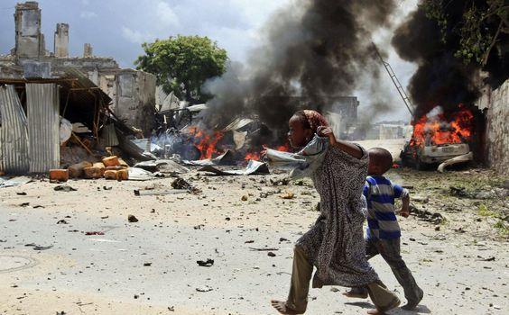 Garota somalia e seu irmão correm após ataque em Mogadício, em 14 de abril