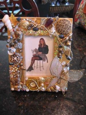 Awesome frame made with vintage jewelry. The artist even did a desk covered in vintage jewelry - wow!