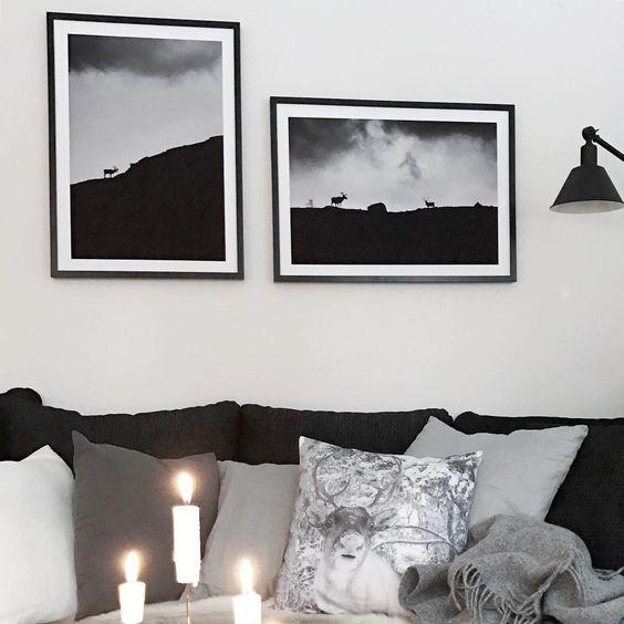 Svartvitt vardagsrum med tända ljus, mönstrade kuddar och inramade ...