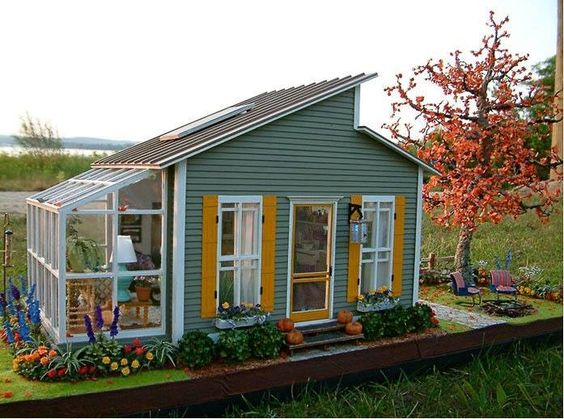 Cute little house/shed with greenhouse. Love the colors!
