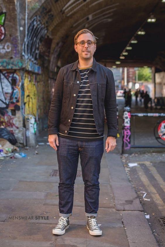 海外メンズブラックデニムジャケットコーデThis is Stu on the streets of London in Spring 2020 wearing, Selvedge Denim Jeans, Green Converse Trainers, Navy Striped T-Shirt, and a Dark Navy Denim Jacket.
