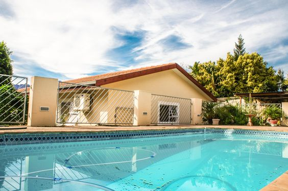 Outside you find an under-roof braai area and a swimming pool enclosed by a security fence.