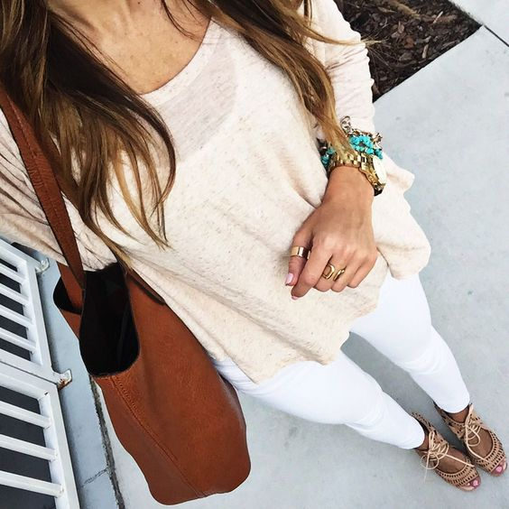 White skinny jeans  beige shirt  neutral strappy heels.