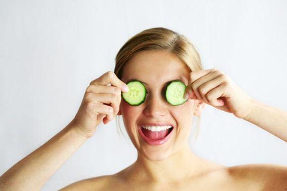 Nackte junge blonde Frau, lachend, hält sich zwei Gurkenscheiben vor Augen, wie Gesichtsmaske, vor weißem Hintergrund