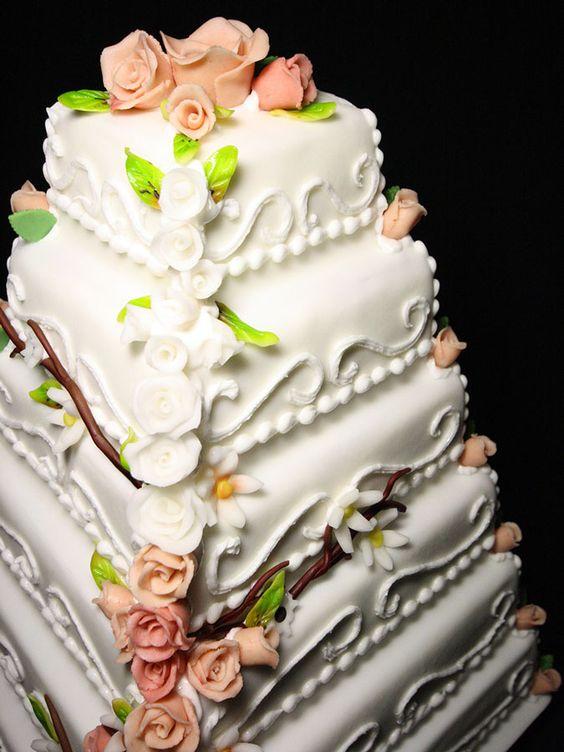 Große Hochzeits-Torte mit mehreren Etagen aus Massa Ticino, aufwändig dekoriert mit Blumen und Ornamenten.