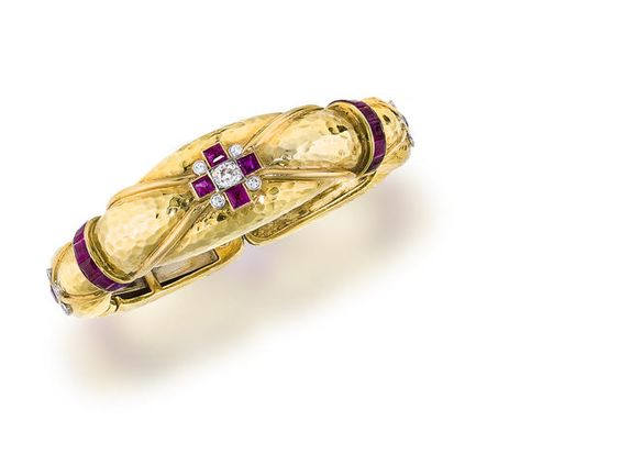 An eighteen karat gold, ruby and diamond bracelet...note the crossed raised wires and the cubed shaped stones