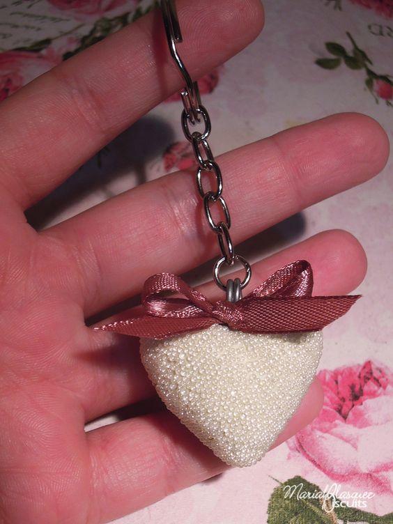 Chaveiro de coração em biscuit com aplicação de micromiçandas peroladas.Detalhe em cetim...