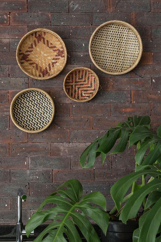 Decoração com influencias brasileiras com madeira e ambientes integrados. Nos detalhes da decoração cestos na parede.