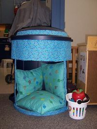 Safe space created by cutting the side of a garbage bin and covering with fabric. Nice and enclosed for kids.