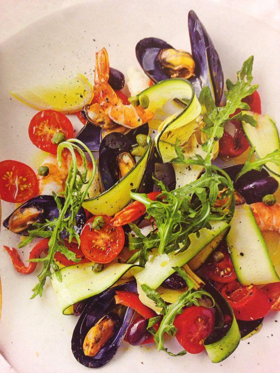 Frisse salade met zeevruchten: gekookte mosselen, garnalen, courgette linten, rucola, tomaat, kalamata olijven, kappertjes, artisjokhart, geroosterde paprika