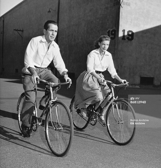 American actor Lauren Bacall and her husband, actor Humphrey Bogart ride bicycles while on the set of the film 'Key Largo', Hollywood, California, 1948. (Photo by KM Archive/Getty Images):