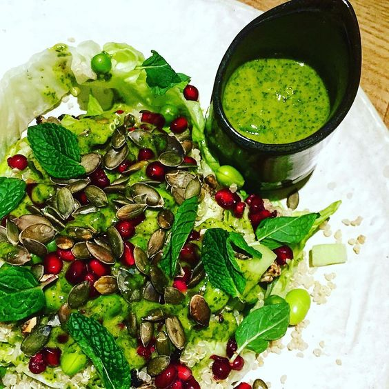 Stay healthy with a salad of green herbs, quinoa, edamame, and pomegranate, topped with Seed + Mill green tahini dressing.