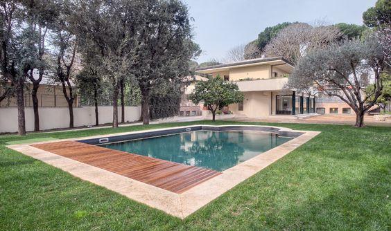 """La piscina è dotata di un moderno sistema avvolgibile a scomparsa sotto la passerella in legno. Per la cura del giardino e per il ricambio dell'acqua della piscina,  segnaliamo che la villa è totalmente autonoma, godendo di una sorgente sotterranea potabile. A fianco, qualche gradino conduce i bagnanti alla """"pool house"""", lo spogliatoio con due docce e due toilette; a bordo piscina si trova una doccia a riscaldamento solare."""