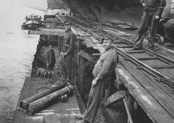 """Wiederherstellung der eingestürzten Ufermauer unter der """"Steinernen Brücke"""". Die Stahlspundwand ist gerammt. Nach Einbringen des Betons der Mauer werden die Spundwandverankerungen an die Wand angeschweißt. Blick von Oberstrom. Transporte per Schiene. Aufnahme aus dem Jahr 1950."""
