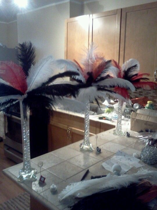 Casino bday decor..made with ostrich feathers , glass beads, tall vases.