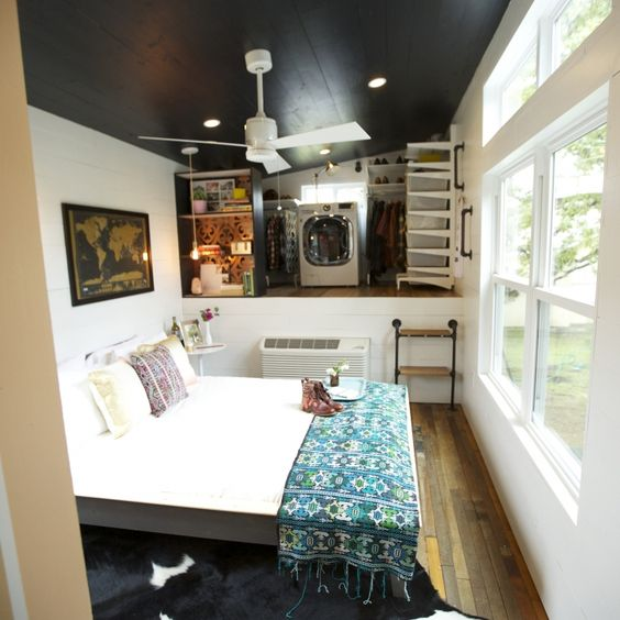 An open bedroom space with an open closet and dual washer for Tiny house washer dryer
