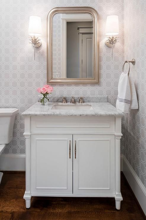 White and gray powder room features walls clad in gray geometric wallpaper lined with a white single washstand topped with carrera marble placed under a silver leaf beaded mirror illuminated by Worlds Away Delilah Silver Wall Sconces.: