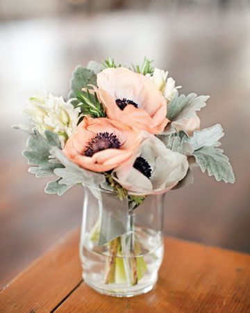 Peach anemones, dusty miller, white hyacinth, and rosemary in glasses.