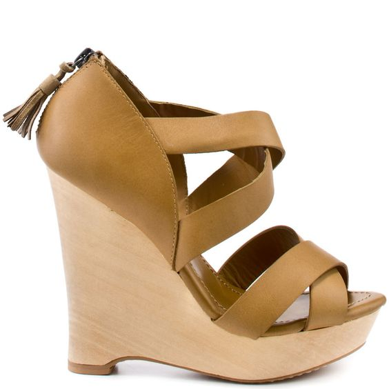 Chic and simple are just a couple of words to describe this stylish wedge.  Sue has a tan leather upper with a light faux 4 1/2 inch wooden heel.  This 1 inch platform sandal has a criss crossing straps at the vamp and a zipper in the back.