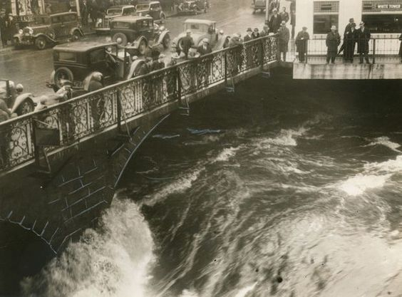 March 12,1936. People gathered at the Main Street Bridge in Pawtucket to watch the river rise. The spring thaw and two days of rain had swollen rivers all over New England, and that night they would overflow their banks in many places.: