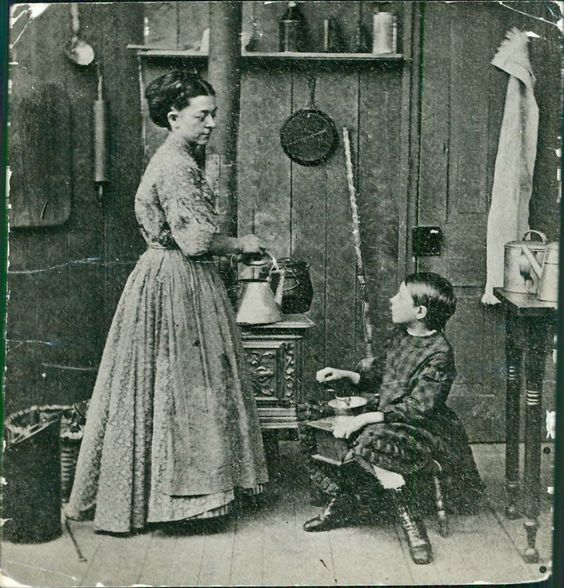 Mother standing by stove and girl grinding coffee.