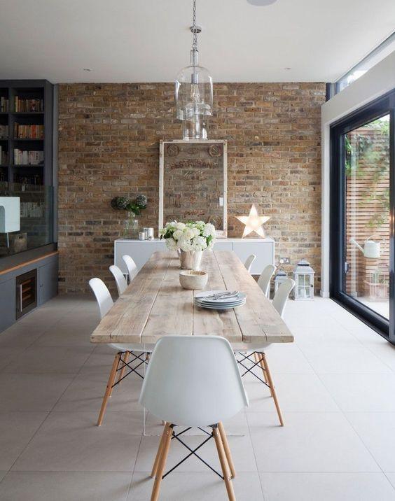 Salle à manger à la fois industrielle et poétique, mur de briques, grandes tuiles au sol.