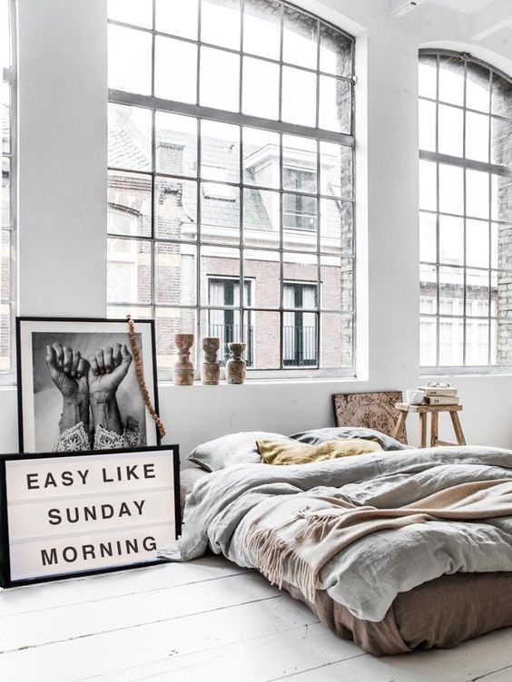"A gorgeous and cozy neutral bedroom with ""Easy Like Sunday Morning"" sign and black and white framed photograph:"