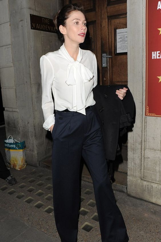 Anna Friel in a white IDA pussybow blouse and wide-leg trousers.