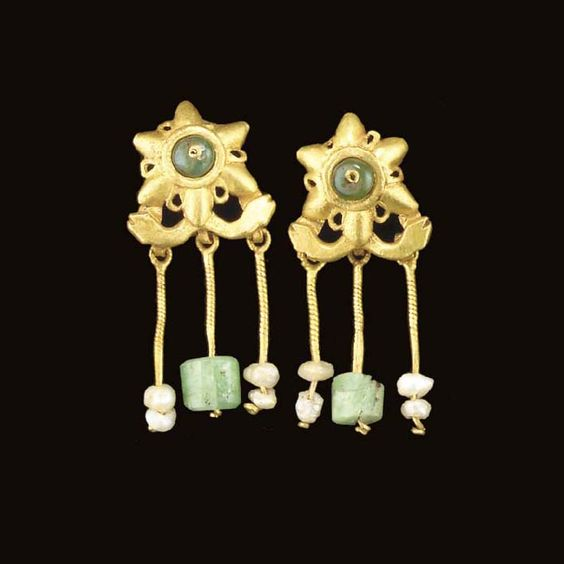 A PAIR OF ROMAN GOLD, EMERALD AND PEARL EARRINGS   Circa 3rd Century A.D.   Each with a six-pointed rosette with small openwork loops between the petals, centered by an emerald bead threaded on to a central wire, a crossbar below of stylized serpent heads, with three suspension loops on the reverse, each with a length of twisted wire, two threaded with two pearls, the central one threaded with an emerald bead, the reverse with an S-shaped earwire: