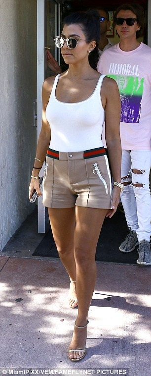 Hot mama: Kourtney showed off her petite frame in a white bodysuit and beige hotpants that had a built in red and navy blue belt