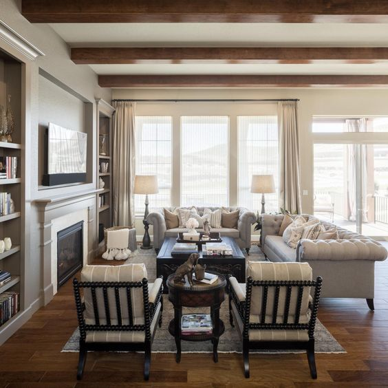 Built-in bookshelves flank the traditional fireplace, while a comfortable seating area combines Chesterfield sofas and neutral striped chairs. Exposed wood beams adds architectural interest to the space.